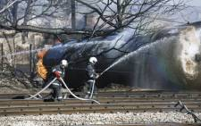 Firefighters spray water on a train which derailed in the northeastern Bulgarian village of Hitrino on December 10, 2016. Picture:  AFP.