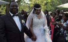 Zimbabwe Prime Minister Morgan Tsvangirai holds hands with his wife Elizabeth Macheka after exchanging vows at a customary law ceremony during their wedding held in Harare on September 15, 2012. Picture: AFP.