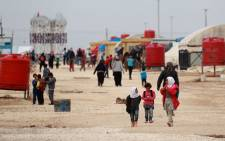 Syrians displaced from Deir Ezzor walk near tents at the al-Mabrouka camp in the northeastern Hasakeh province on 19 November 2018. Picture: AFP