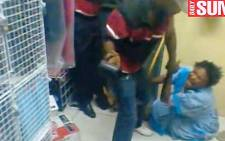 A screengrab from an exclusive Daily Sun video which shows an elderly woman being beaten with a belt and rubber hammer.
