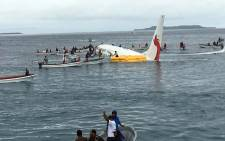 This picture taken by James Yaingeluo on 28 September, 2018 shows locals approaching to rescue passengers of the crashed Air Niugini aircraft on the remote Island of Weno, in Micronesia. Picture: James Yaingeluo/AFP