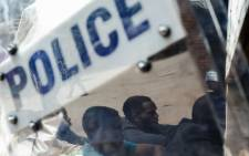 FILE: Zimbabwean anti-riot police forces watch men, arrested during violent protests triggered by a sudden rise in fuel prices announced by Zimbabwean President, for their hearing at the Law Court in the capital Harare, on 16 January 2019. Picture: AFP