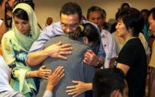 FILE: Malaysia's Minister of Defence and Acting Transport Minister Hishammuddin Hussein (C) hugs a relative of the missing Malaysia Airlines flight MH370 during his visit at a hotel in Putrajaya on March 29, 2014. Picture: AFP.