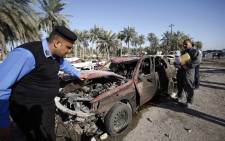 Iraqi emergency responders inspect debris at the site of a truck bomb, that exploded at a crowded checkpoint, in the Iraqi city of Hilla, south of Baghdad on 6 March, 2016. Picture: AFP.