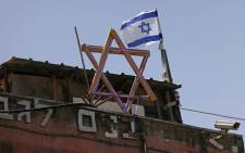 FILE: The Star of David and an Israeli flag are seen on top of a house in the Sheikh Jarrah neighbourhood of occupied east Jerusalem on 5 May 2021. Israeli Jews backed by courts have taken over houses in Sheikh Jarrah in east Jerusalem on the grounds that Jewish families lived there before fleeing in Israel's 1948 war for independence. Picture: Emmanuel DUNAND/AFP