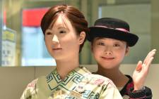 FILE: A department store employee poses with humanoid ChihiraAico (L) clad in a Japanese kimono in Tokyo on 20 April, 2015. Picture: AFP