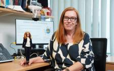 """An undated handout picture released on 3 August 2021 shows Sarah Gilbert posing with a Barbie doll in her image. Toy giant Mattel said today it hoped to """"inspire the next generation"""" after creating a model of its iconic Barbie doll in honour of Sarah Gilbert, co-creator of the Oxford/AstraZeneca coronavirus vaccine. Picture: Mattel AFP"""