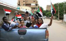 Sudanese children wave small national flags as people celebrate outside the Friendship Hall in the capital Khartoum where generals and protest leaders signed a historic transitional constitution meant to pave the way for civilian rule in Sudan, on 17 August 2019.  Picture: AFP
