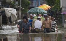 Local Muslim residents wade through floodwaters with the coffin of an elder who passed away (death not related to floods) near the Chao Phraya river in Thailand on 14 September 2011. AFP