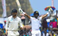 Sri Lanka's cricket team captain Dimuth Karunaratne (R) celebrates after scoring a century (100 runs) during the final day of the first Test cricket match between Sri Lanka and New Zealand at the Galle International Cricket Stadium in Galle on 18 August 2019.  Picture: AFP