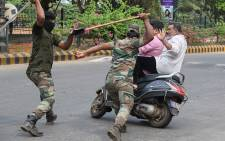 Members of the Karnataka Reserve Police Force swing their sticks to beat two men on a scooter who rode too close to a barricade set up on a street in Mangalore on 20 December 2019, amid heightened security due to protests over India's new citizenship law. Picture: AFP