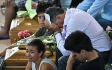 Relatives mourn next to a coffin during a funeral service for victims of the Italy earthquake. Picture: AFP.