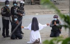 This handout photo taken on March 8, 2021 and released on March 9 by the Myitkyina News Journal shows a nun pleading with police not to harm protesters in Myitkyina in Myanmar's Kachin state, amid a crackdown on demonstrations against the military coup. Picture: Handout / Myitkyina News Journal / AFP.