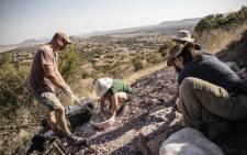 Wits University Professor Jonah Choiniere (left) prepares a cast to jacket rock formations containing fossils on 11 October 2018 at the Heelbo farm on the outskirts of Rosendal, South Africa. Picture: AFP.