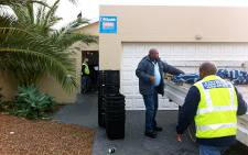 Department of Fisheries and SAPS begin loading a truck with abalone processing equipment in Sunset Beach. Graeme Raubenheimer/EWN