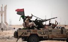 Libyan rebel fighters flash the victory sign as they drive on 11 June 2011 in Ajdabiya. AFP