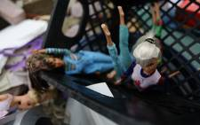 Barbie dolls sit in a create. Picture: AFP