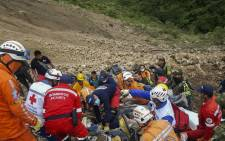 Handout picture released by Colombia's National Police press office showing rescuers look for the bodies of the passengers of a bus that was buried by a landslide on the road between the municipalities of Junin and Tuquerres, department of Narino, southwest of Colombia, on 21 January 2018. Picture: AFP.
