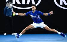 Serbia's Novak Djokovic hits a return against France's Lucas Pouille during their men's singles semi-final match on day 12 of the Australian Open tennis tournament in Melbourne on 25 January, 2019. Picture: AFP.