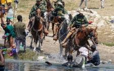 In this file photo United States Border Patrol agents on horseback try to stop Haitian migrants from entering an encampment on the banks of the Rio Grande near the Acuna Del Rio International Bridge in Del Rio, Texas on 19 September 2021. Picture: Paul Ratje/AFP