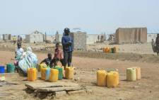 FILE: Malian refugees gather to collect water at the Malian Goudebou refugee camp near Dori, North Eastern Burkina Faso, on 11 March 2021 a year after fleeing the threat of jihadist attacks. Picture: Armel Baily/AFP