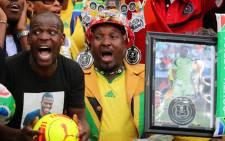 FILE: outh African supporters hold a portrait of murdered Bafana Bafana captain and goalkeeper Senzo Meyiwa. Picture: AFP.