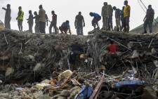 Nigerian rescue workers searching through rubble from the collapsed guesthouse at the Synagogue Church of All Nations in Lagos on 16 September 2014. Picture: EPA.