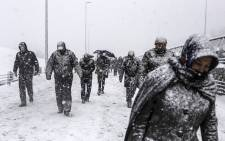 People walk during heavy snowfall in Istanbul on 18 February 2015. Istanbul woke up to find the famed minarets and domes of the historic city's skyline covered in snow after a heavy overnight fall that has still shown no sign of abating. Picture: AFP.