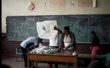 An electoral officer empties a ballot box during the counting of the ballots for the second round of Madagascar's presidential election at a polling station in Antananarivo on 19 December 2018. Madagascar voted on 19 December in a two-man contest between former presidents who have waited years to come face-to-face in a fiercely personal battle for power in the Indian Ocean island. Picture: AFP