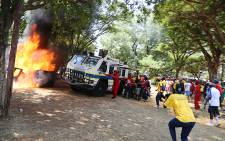 A group of students charge towards a police nyala blocking a blazing portable toilet during a student protest over proposed tuition fee hikes for the 2016 year at the Union Buildings in Pretoria on 23 October 2015. Picture: Reinart Toerien/EWN.
