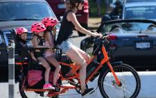 A woman and three children go on a cooling bike ride on a scorching hot day, in Vancouver, British Columbia, June 29, 2021. Schools and Covid-19 vaccination centers closed Monday while community cooling centers opened as western Canada and parts of the western United States baked. Picture: AFP.