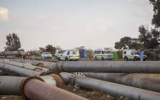 Police stand guard along the road between Reiger Park and Ramaphosa where community members fought with police over the cutting of illegal electricity connections. Picture: Thomas Holder/EWN.
