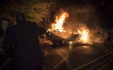 A security guard attempts to extinguish a UCT vehicle after #RhodesMustFall protesters set it alight. Picture: Thomas Holder/EWN