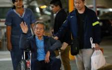 FILE: Peru's former President Alberto Fujimori waves to supporters beside his son, Congressman Kenji Fujimori (R), as he is wheeled out of the Centenario Clinic in Lima on 4 January 2018. Picture: AFP
