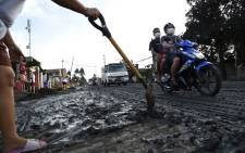 A resident uses a shovel to clear mud and ash spewed by Taal volcano at a development in Tanauan town, Batangas province south of Manila on 13 January 2020. Picture: AFP