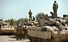 Israeli soldiers work on their Merkava tanks at an army deployment point near the Israeli-Gaza border on 20 August,2014. Picture: AFP.