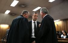 Oscar Pistorius speaks with his lawyers prior to attend a hearing of his trial at the High Court in Pretoria on March 5, 2014. Picture: AFP.