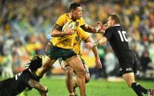 Wallabies fullback Israel Folau (C) pushes away New Zealand All Blacks fly-half Aaron Cruden (R) during their rugby union Test match in Sydney on 16 August 2014. Picture: AFP.