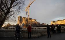 A picture taken on 19 December 2019 shows cranes outside the Notre-Dame Cathedral in Paris, which was partially destroyed when a fire broke out beneath the roof on 15 April  2019. Picture: AFP