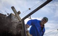 Moses Kobi salvages pieces from his destroyed home in White Location, Knysna, on 20 August 2017 that was burnt during the fires in June. It will be four months before his home is replaced. Picture: Thomas Holder/EWN