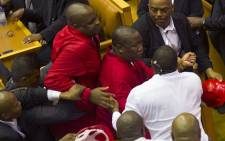 FILE: EFF leader Julius Malema (C) and members of his party clash with security forces. Captain Walter Prins is seen in the black suit manhandling Malema during the Sona on February 12, 2015. Picture: AFP.