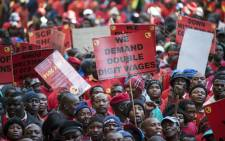 FILE: Striking workers hold placards as they demonstrate on the first day of a nationwide strike on 1 July, 2014. Picture: AFP.