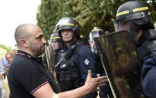 A taxi driver (L) argues with riot policemen standing guard at the Porte Maillot traffic roundabout on 25 June, 2015 in Paris. Picture: AFP.