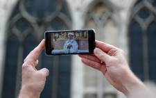 A man holds a smartphone showing a live broadcast of Archbishop of Paris Michel Aupetit holding the first mass of the Notre-Dame de Paris cathedral on June 15, 2019, two months after the April 15 fire, in Paris. Picture: AFP.
