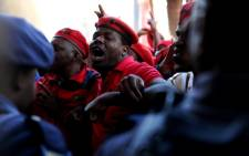 EFF members push their way past policemen into the Gauteng Provincial Legislature in Johannesburg during a protest march on 22 July 2014. Picture: Sapa.