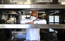 French chef Guy Savoy poses with a face mask in the empty kitchen of his Guy Savoy restaurant at La Monnaie de Paris in Paris on 19 May 2020. Picture: AFP.