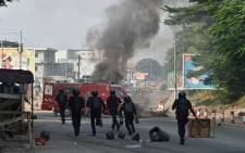 Ivorian anti-riot police arrive to disperse young demonstrators that burnt barricades in the road during a protest against the third term of Ivory Coast President Alassane Ouattara in the Riviera Anono district of Abidjan on 13 August 2020, ahead of country's presidential election in October 2020. Picture: AFP