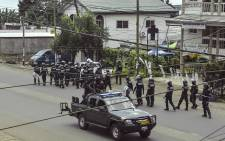 Cameroon police officials with riot equipment patrol along a street in the administrative quarter of Buea some 60kms west of Douala on 1 October, 2017. Picture: AFP.