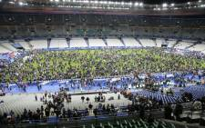 Spectators wait on the pitch of the Stade de France stadium in Seine-Saint-Denis, Paris suburb on 13 November, 2015 after a series of gun attacks occurred across Paris as well as explosions outside the national stadium where France was hosting Germany. Picture: AFP.