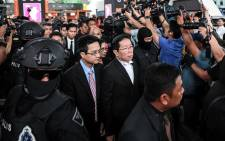 Gooi Soon Seng (C), lawyer for Indonesian defendant Siti Aisyah is escorted by police personnel at the low-cost carrier Kuala Lumpur International Airport 2 (KLIA2) in Sepang during a visit to the scene of the murder as part of the Shah Alam High Court trial process on 14 October 2017. Picture: AFP.